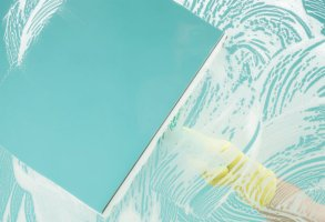 cropped image of woman wiping soap from glass using squeegee