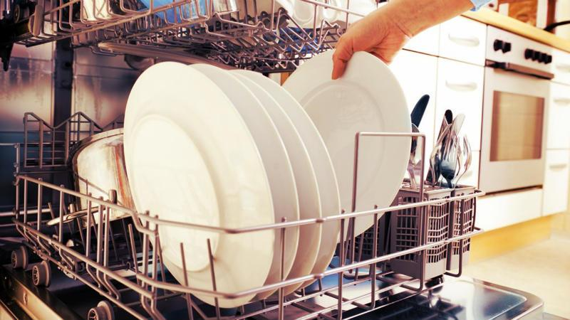 cropped image of a woman lining up plates in dishwasher