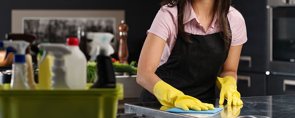 cropped image of woman with black apron wiping countertop