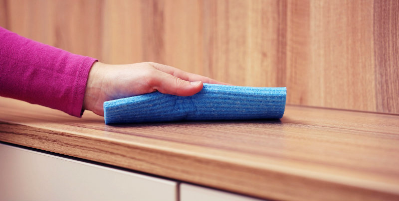 cropped image of a woman wiping wooden countertop