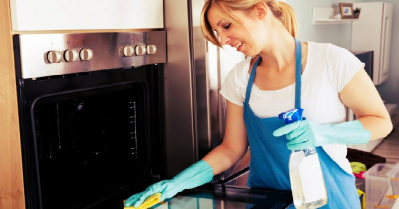 happy woman wiping oven grill and door