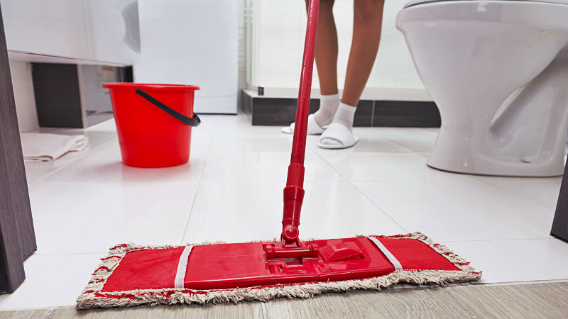 cropped image of a young woman mopping bathroom floor