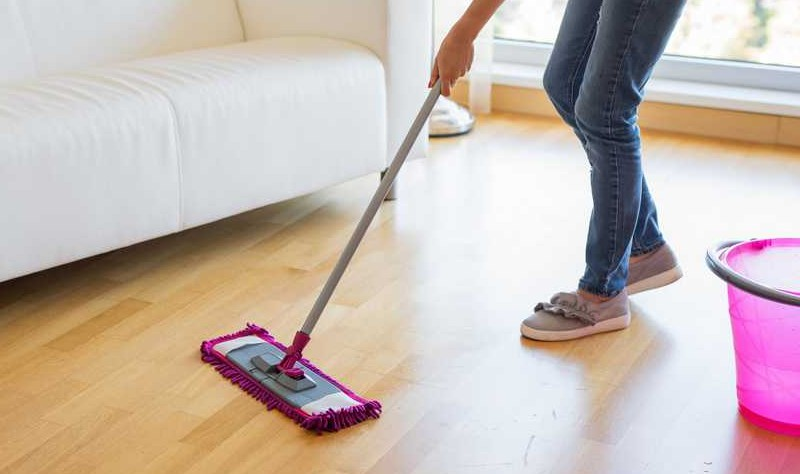 cropped image of a woman moping a wooden floor