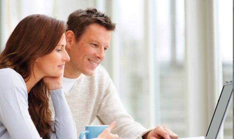 happy couple reading something on a laptop