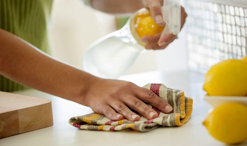 cropped image of a woman disinfecting a surface with a spray bottle and cloth rag