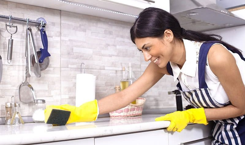 young woman wiping the kitchen surface with a sponge