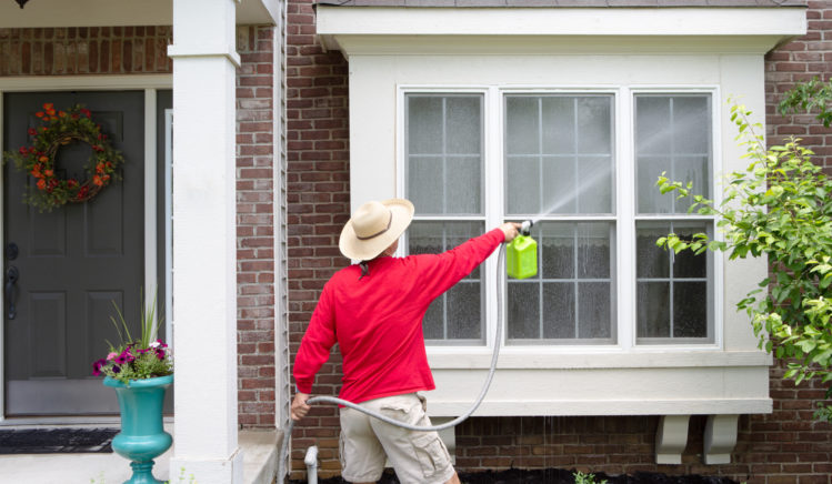 Young man with a water pipe washing the window glass