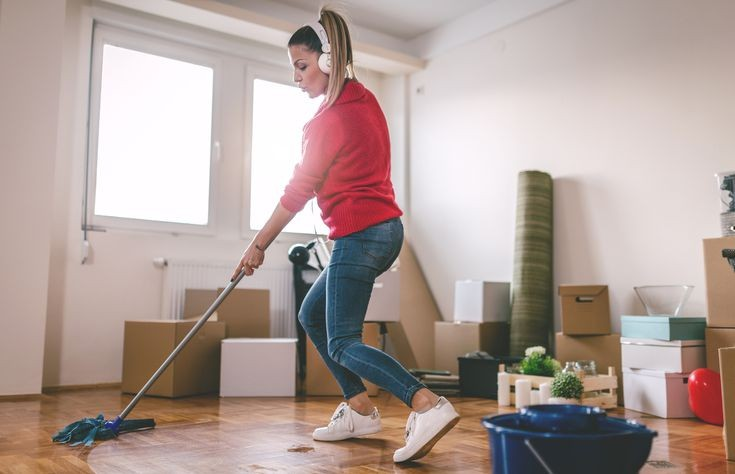 young woman sweeping her floor with a wiper