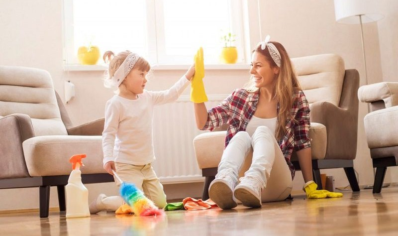 young woman wearing yellow gloves sitting on the floor with her daughter