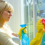 woman wiping window glass with a cloth