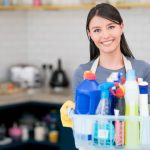 woman with a basket full of spray bottles and cloth mop