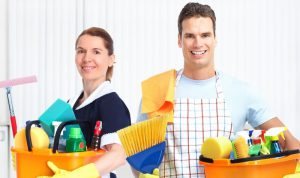 Young professional couple holding buckets full or spray bottles and brushes