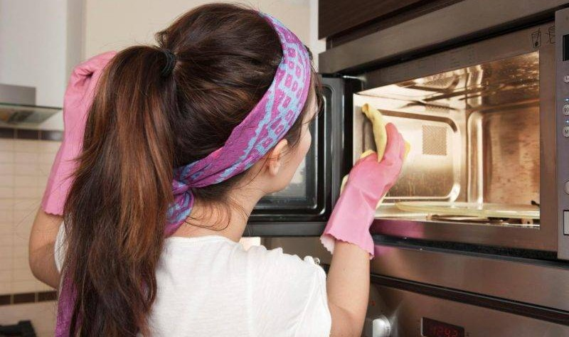 young woman wiping an oven with a cloth mop