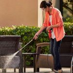 woman holding a pressure water pipe and washing the outdoor
