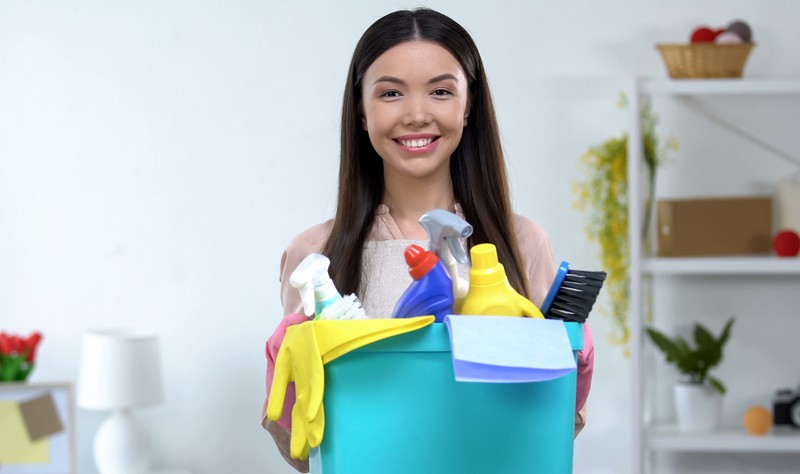 young woman with a bucket full of chemical bottles and spray bottles