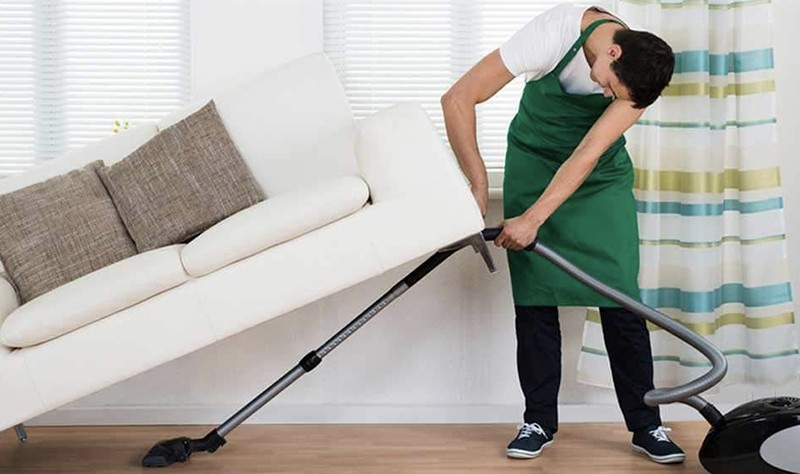 young professional trying to vacuum under a couch