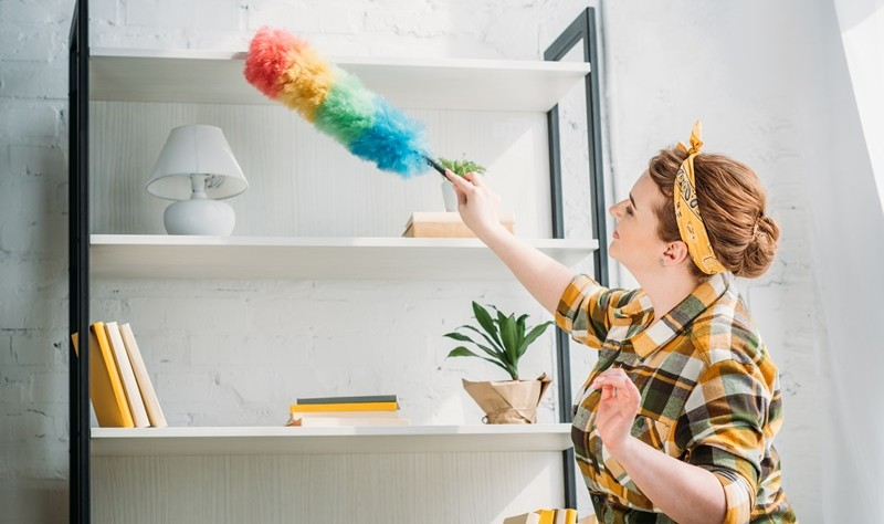 young woman dusting a her room with a duster