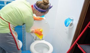 young woman wiping a toilet seat with a cloth mop
