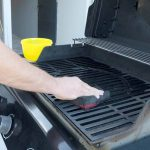 cropped picture of a young man wiping a BBQ grill