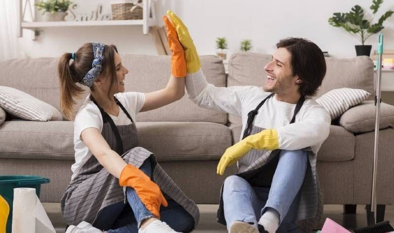 young couple wearing gloves sitting on the floor